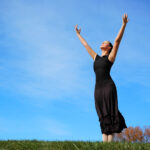 Ballerina dressed in black with arms extended toward heaven